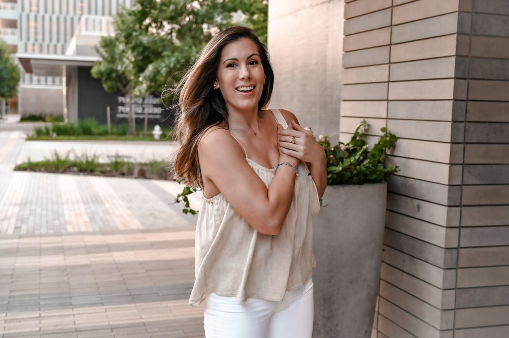 Houston style blogger Maria Munoz smiling while clutching purse on shoulder