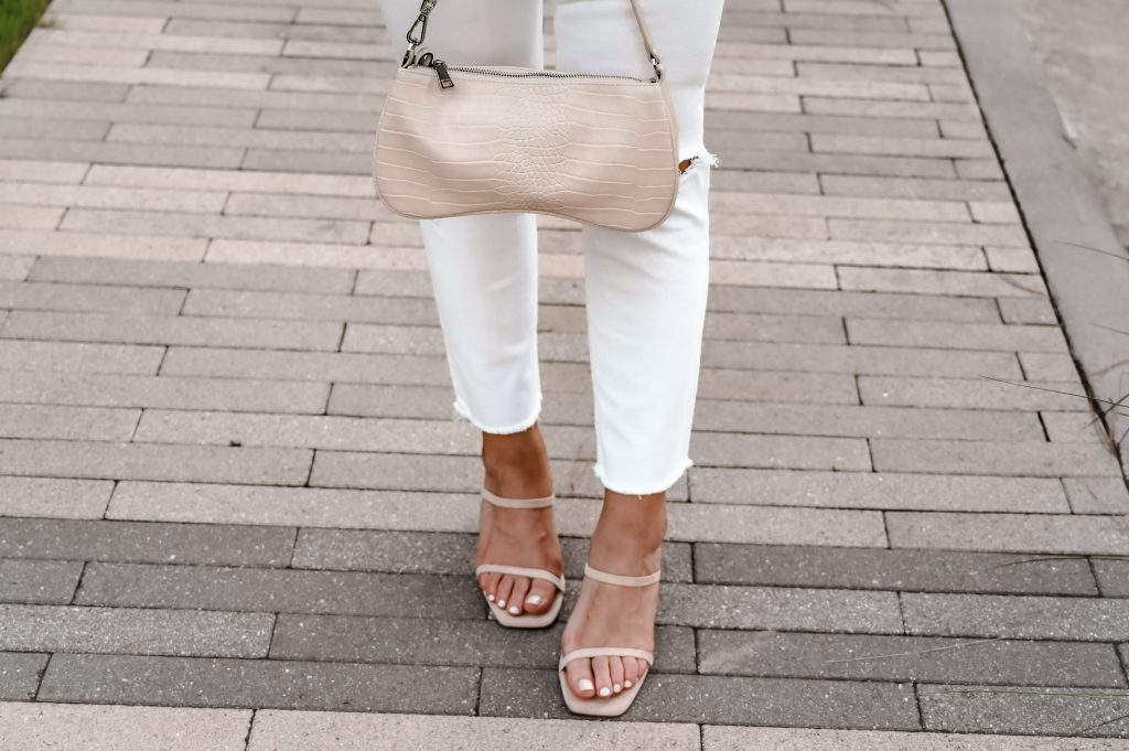 Cream purse with tan colored strappy heels